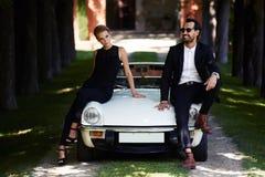 Coppie romantiche ed alla moda che posano sull'automobile di lusso del cabriolet all'aperto di estate fotografie stock