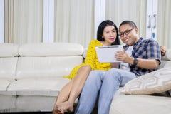Coppie romantiche facendo uso di una compressa digitale a casa immagine stock libera da diritti