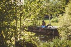Coppie romantiche felici nel villaggio, passeggiata sul ponte di legno vicino al lago L'uomo sul rivestimento di una giovane donn fotografia stock