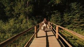 Coppie romantiche nell'amore in vestiti ricamati tradizionali che camminano sul ponte di legno in Carpathians e felicemente stock footage