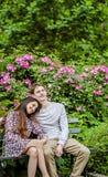 Coppie romantiche sul banco in giardino Immagine Stock