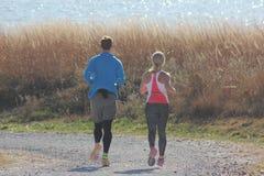 Coppie sane che pareggiano intorno al lago fotografia stock libera da diritti