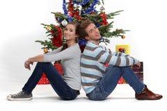 Coppie sedute dall'albero di Natale Fotografie Stock Libere da Diritti
