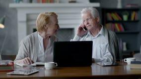 Coppie senior anziane felici facendo uso del computer portatile e dello smartphone video d archivio