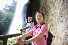 Coppie senior asiatiche che fanno un'escursione nella montagna con la cascata Fotografia Stock Libera da Diritti