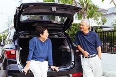 Coppie senior asiatiche felici che stanno sul retro dell'automobile di SUV, esaminandose con il sorriso e la felicità fotografia stock