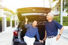 Coppie senior asiatiche felici che stanno sul retro dell'automobile di SUV, indicante su nel cielo con il sorriso e la felicità immagini stock libere da diritti