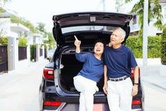 Coppie senior asiatiche felici che stanno sul retro dell'automobile di SUV, indicante su nel cielo con il sorriso e la felicità fotografia stock