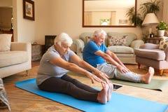 Coppie senior attive che allungano insieme mentre facendo yoga a casa Fotografia Stock Libera da Diritti