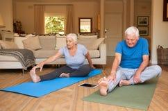 Coppie senior attive che allungano mentre facendo yoga insieme a casa Immagini Stock Libere da Diritti