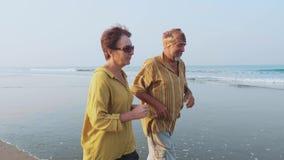 Coppie senior attive che corrono sulla spiaggia sabbiosa all'alba video d archivio