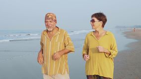 Coppie senior attive che corrono sulla spiaggia sabbiosa all'alba stock footage