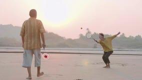 Coppie senior attive che giocano la palla di impulso di 'chi' del tai alla spiaggia stock footage