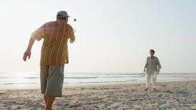 Coppie senior attive che giocano la palla di impulso di 'chi' del tai alla spiaggia al rallentatore archivi video
