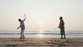 Coppie senior attive che giocano la palla di impulso di 'chi' del tai alla spiaggia al rallentatore stock footage