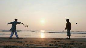 Coppie senior attive che giocano la palla di impulso di 'chi' del tai alla spiaggia al rallentatore video d archivio