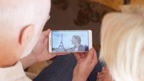 Coppie senior a casa che hanno video chiacchierata con la figlia dello studente da Parigi, torre Eiffel su fondo video d archivio