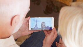 Coppie senior a casa che hanno video chiacchierata con la figlia dello studente da Parigi, torre Eiffel su fondo stock footage