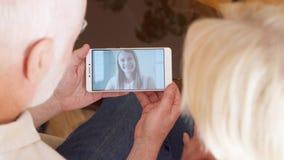 Coppie senior a casa che hanno video chiacchierata via la chiamata di app del messaggero sul cellulare con la loro figlia all'est stock footage