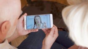 Coppie senior a casa che hanno video consultazione di chiacchierata via la chiamata di app del messaggero sul cellulare con il me video d archivio