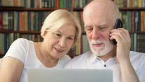 Coppie senior a casa con il computer portatile Famiglia pensionata dei pensionati facendo uso del telefono che discute smth sullo stock footage