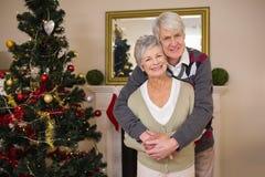 Coppie senior che abbracciano accanto al loro albero di Natale Fotografia Stock
