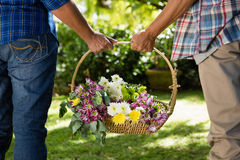 Coppie senior che camminano nel giardino con il canestro del fiore Immagine Stock