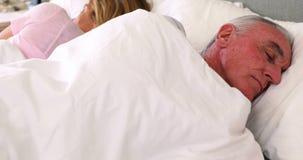 Coppie senior che dormono sul letto stock footage
