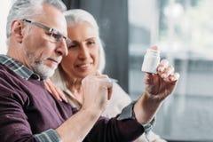 Coppie senior che esaminano la bottiglia di pillola a disposizione fotografie stock