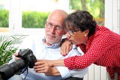 Coppie senior che esaminano le immagini sullo schermo della macchina fotografica Immagini Stock Libere da Diritti