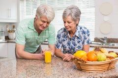 Coppie senior che esaminano vetro di succo d'arancia Immagini Stock Libere da Diritti