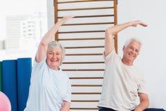 Coppie senior che fanno allungando esercizio nello studio di forma fisica Fotografia Stock Libera da Diritti