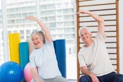 Coppie senior che fanno allungando esercizio in palestra Immagini Stock Libere da Diritti