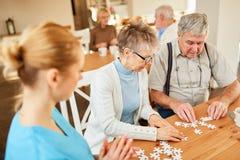 Coppie senior che giocano puzzle nella casa di riposo fotografia stock