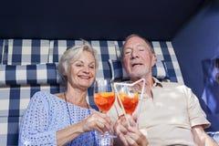 Coppie senior che godono del pensionamento nella sedia di giardino di estate Fotografie Stock Libere da Diritti