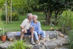 Coppie senior che godono dell'estate in giardino Fotografia Stock Libera da Diritti