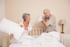 Coppie senior che hanno una lotta di cuscino Fotografie Stock