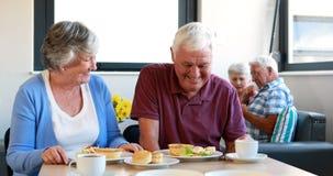 Coppie senior che interagiscono a vicenda mentre mangiando prima colazione stock footage