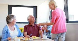 Coppie senior che interagiscono a vicenda mentre mangiando prima colazione archivi video
