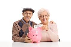 Coppie senior che mettono soldi in un porcellino salvadanaio fotografia stock