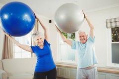 Coppie senior che si esercitano con la palla di esercizio Immagine Stock