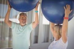 Coppie senior che si esercitano con la palla di esercizio Immagini Stock