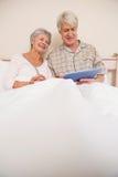 Coppie senior che si rilassano a letto facendo uso del pc della compressa Immagine Stock Libera da Diritti