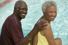 Coppie senior che si siedono dal ritratto della piscina. immagine stock