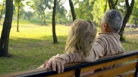 Coppie senior che si siedono sul banco, godente insieme del fine settimana della campagna, viaggio fotografie stock
