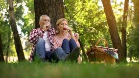 Coppie senior che si siedono sull'erba e sul vino bevente, data romantica, anniversario fotografie stock libere da diritti