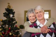 Coppie senior che sorridono accanto al loro albero di Natale Immagini Stock Libere da Diritti
