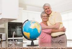Coppie senior che sorridono alla macchina fotografica insieme al globo Immagine Stock