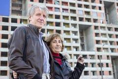 Coppie senior che stanno con le chiavi della casa a disposizione contro la costruzione di appartamento Fotografia Stock Libera da Diritti