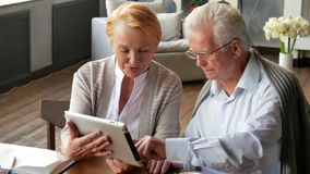 Coppie senior che websurfing su Internet con la compressa Uomo e donna anziani felici che per mezzo del computer della compressa video d archivio